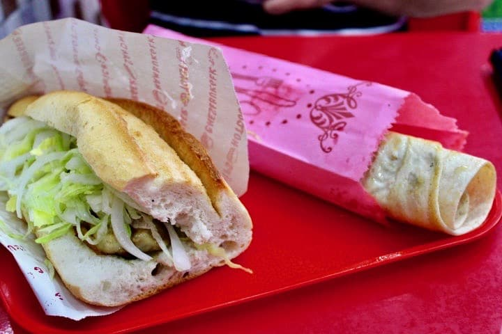 Turkish Food in Istanbul: Two fish sandwiches, foods to eat in Istanbul. One is a wrap and one is a roll, both are served in paper on a red tray.