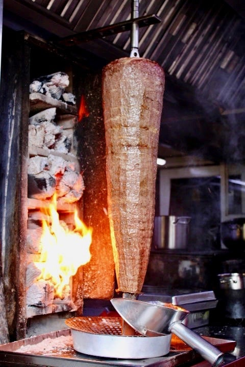 Turkish food in Istanbul: Iskender kebab being cooked next to a coal fire in Istanbul