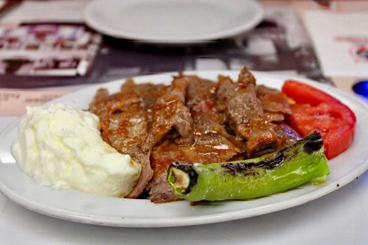 Turkish food in istanbul: Iskender kebab, one of the foods to eat in Istanbul. Juicy meat is served with a grilled pepper on a plate and is covered in a shiny butter sauce.
