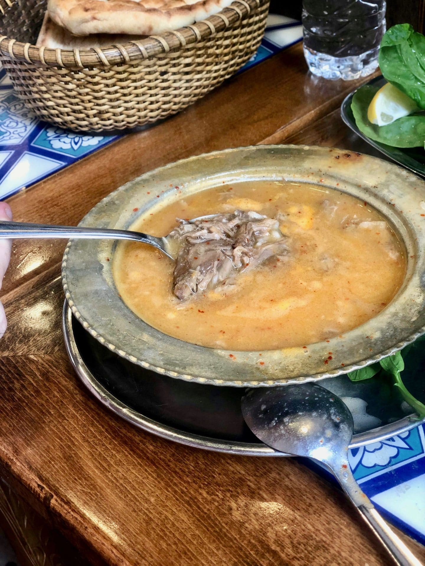 Turkish Food in Istanbul: Beyran çorbasi - lamb soup. The soup is an orange colour and a spoon is holding up a chunk of lamb.