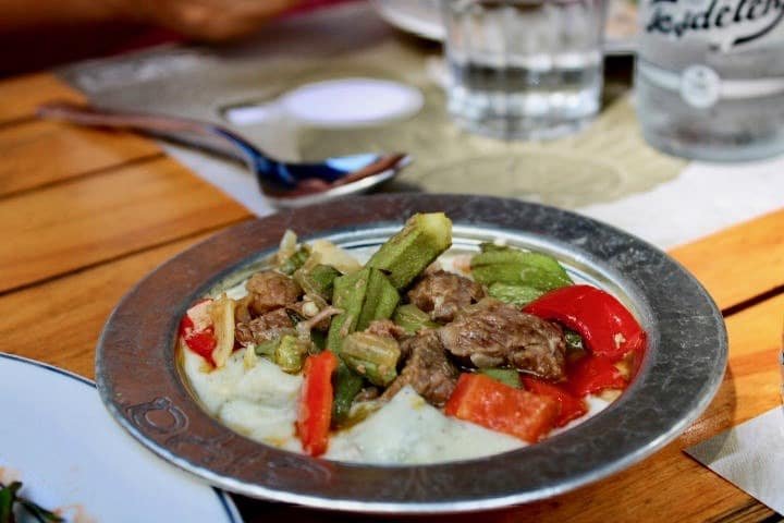 Turkish food in Istanbul: A bowl of lamb, okra and bright red peppers served on a creamy rice base. Things to eat in Istanbul.