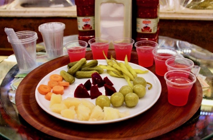Turkish food in Istanbul: A plate of pickled vegetables and cups of bright pink pickle juice, tried in a pickle shop