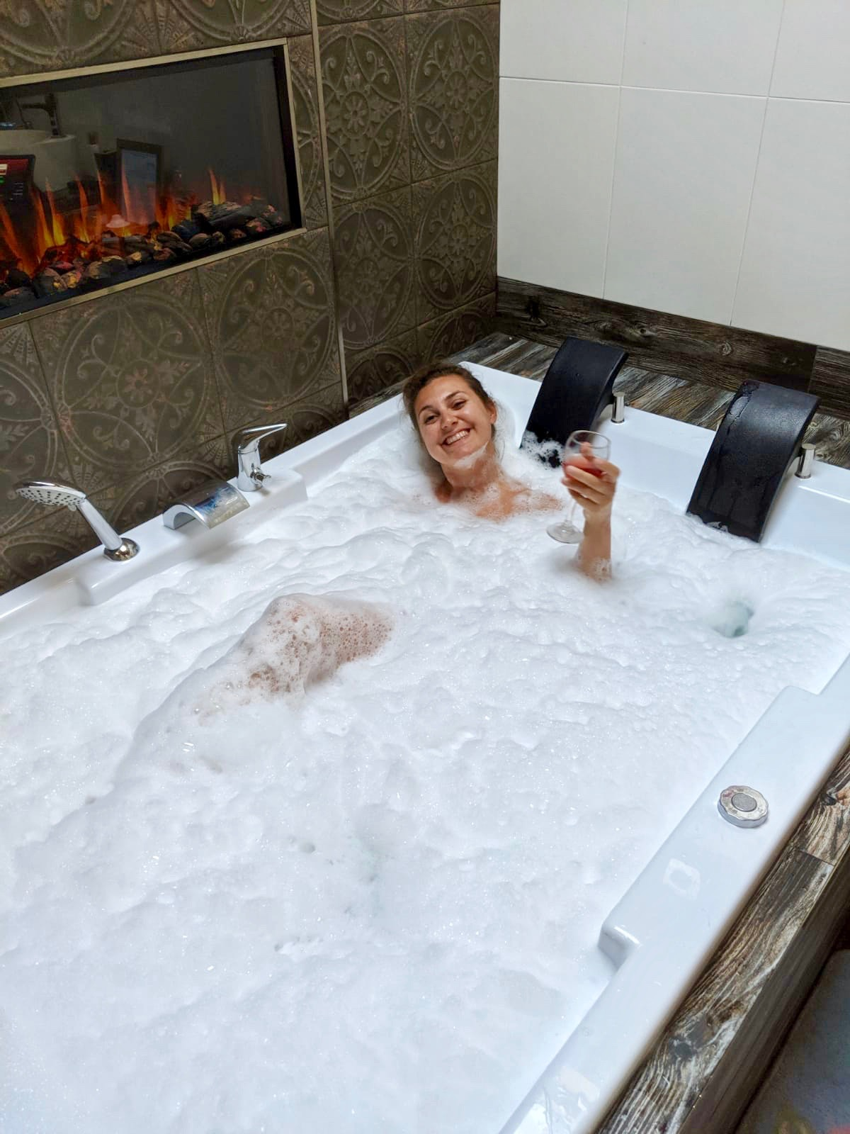 Girl in double sized jacuzzi bath holding a glass of wine. She is covered up to her neck by bubbles.