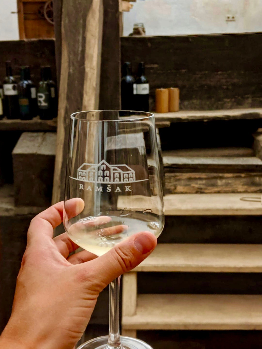 glass of white wine with Chateau Ramsak branding on, taken inside the wine cellar with the largest wine press in Europe in the background