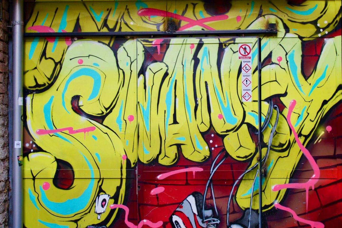 A graffiti wall in a courtyard at Swanky Hostel, with the word Swanky in bright colours
