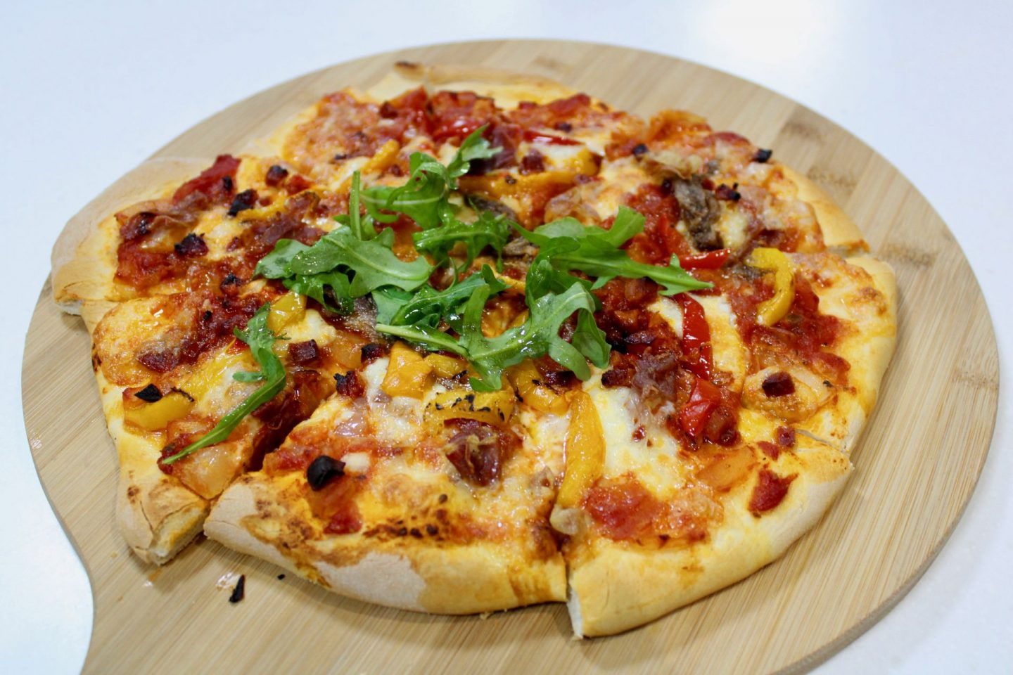 Cooked pizza on a wooden board. The edges are crispy, the cheese is perfectly melted and the pizza is topped with fresh rocket.