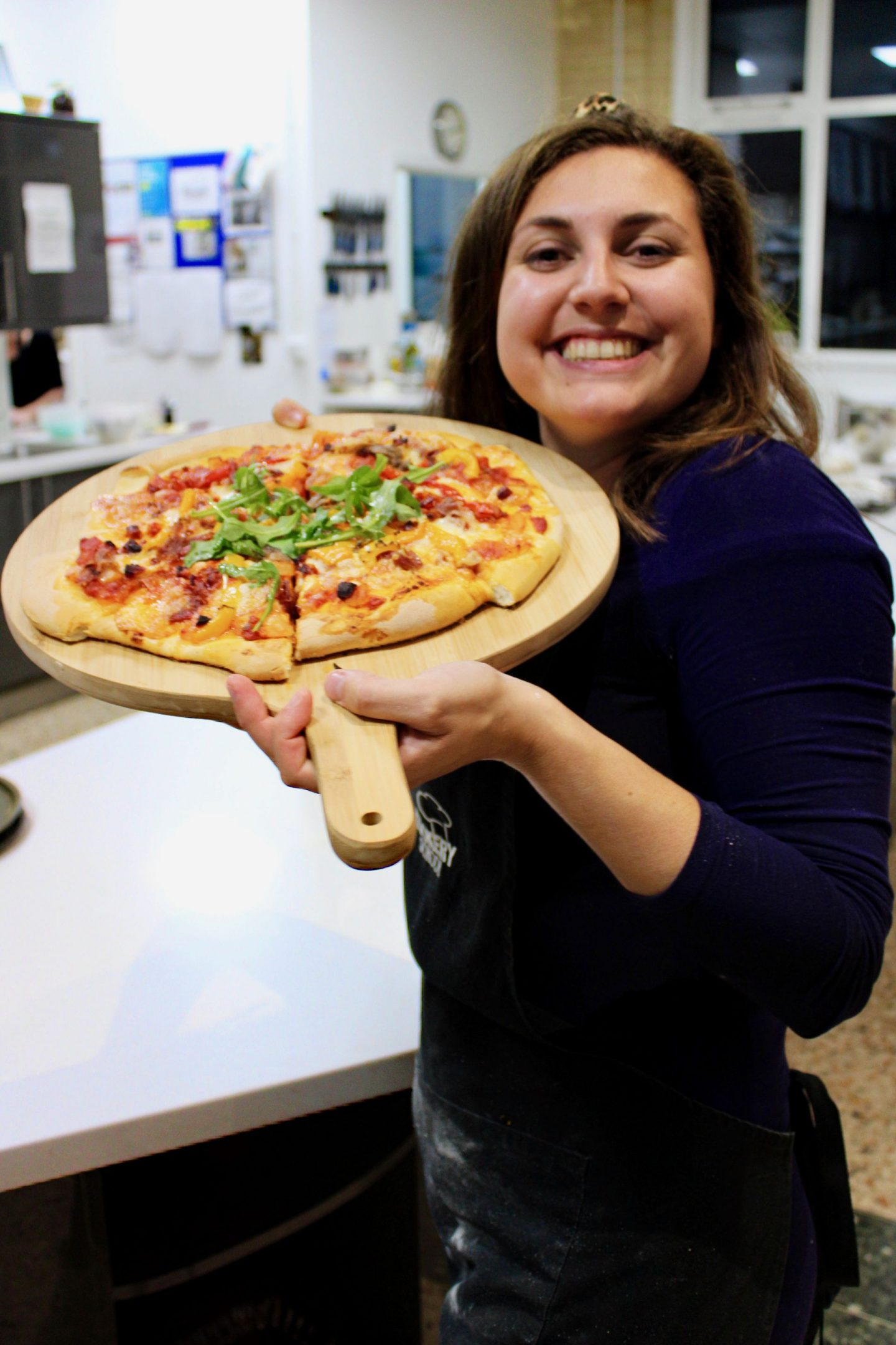 Girl in blue dress holding up the pizza she made at Leeds Cookery School and smiling