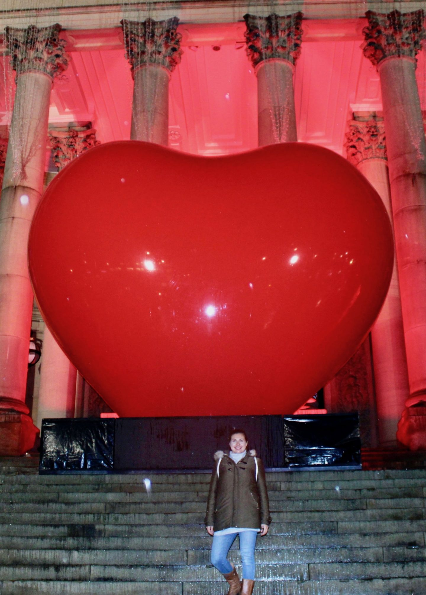 Girl stood in front of 'with love' installation at Leeds Light Night. She's wearing a brown coat and jeans and is stood at the bottom of some steps with a giant red heart behind her