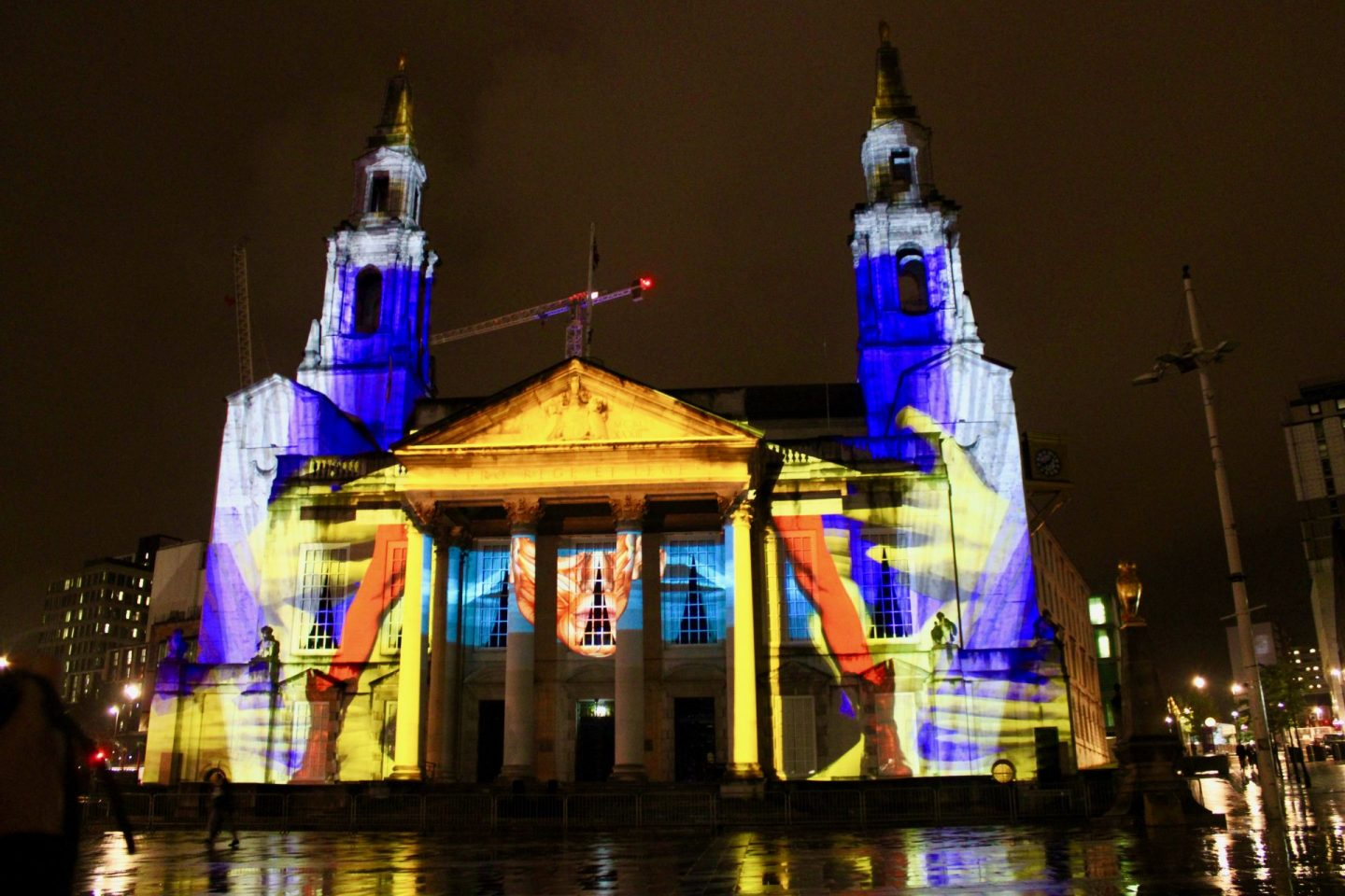 Leeds Civic Hall illuminated with an animated projection at Leeds Light Night. There are colours of yellow, red and purple showing various patterns, and some of the colours are reflecting off the ground in front of the building
