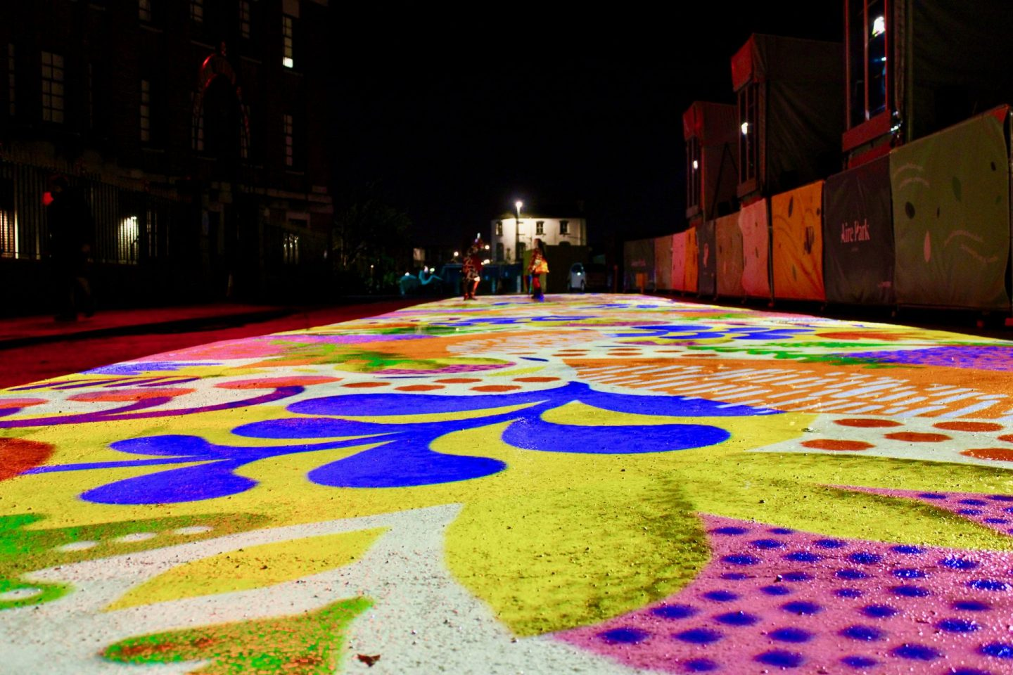 A long range shot from ground level showing a colourful projection on the floor as part of Leeds Light Night