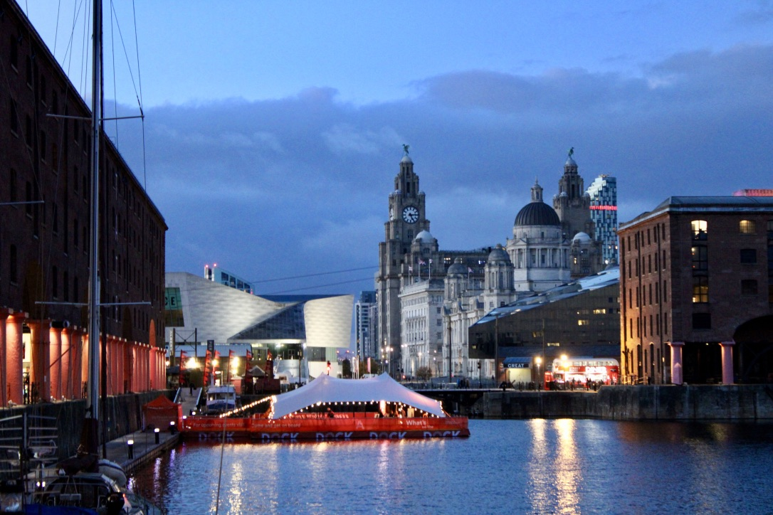 Royal Albert Docks in Liverpool taken at dusk, with the floating cinema in the foreground and Liver building in the background