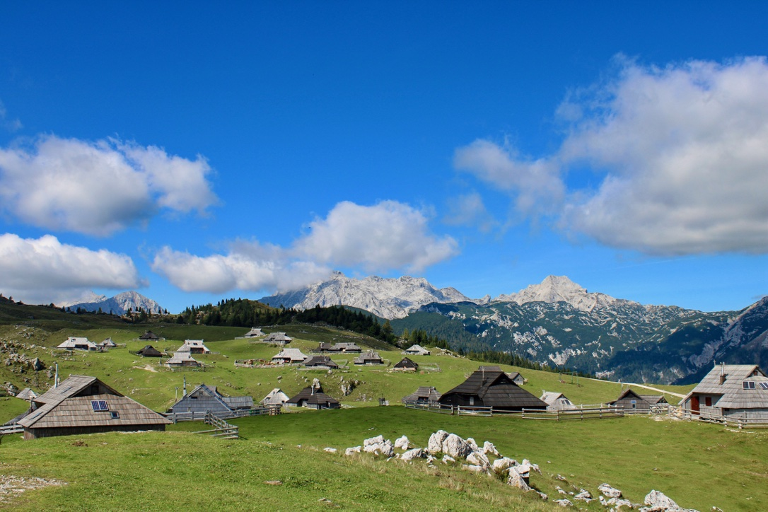 Valika Planina near Kamnik in the Ljubljana region. Image shows herdsman huts on green pasture with mountains in the background.