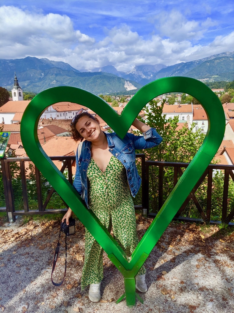 Nell posing in a feel slovenia love heart with views of Kamnik and the alps in the background