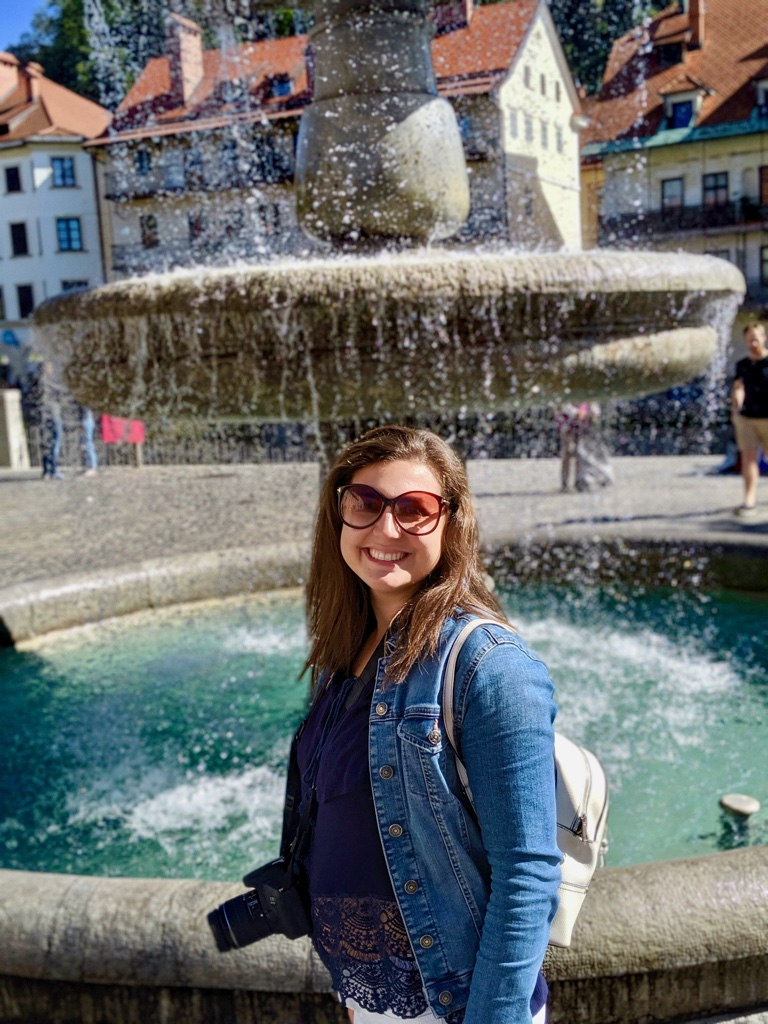 Nell stood in front of a fountain during her 24 hour stay in Ljubljana, smiling at the camera