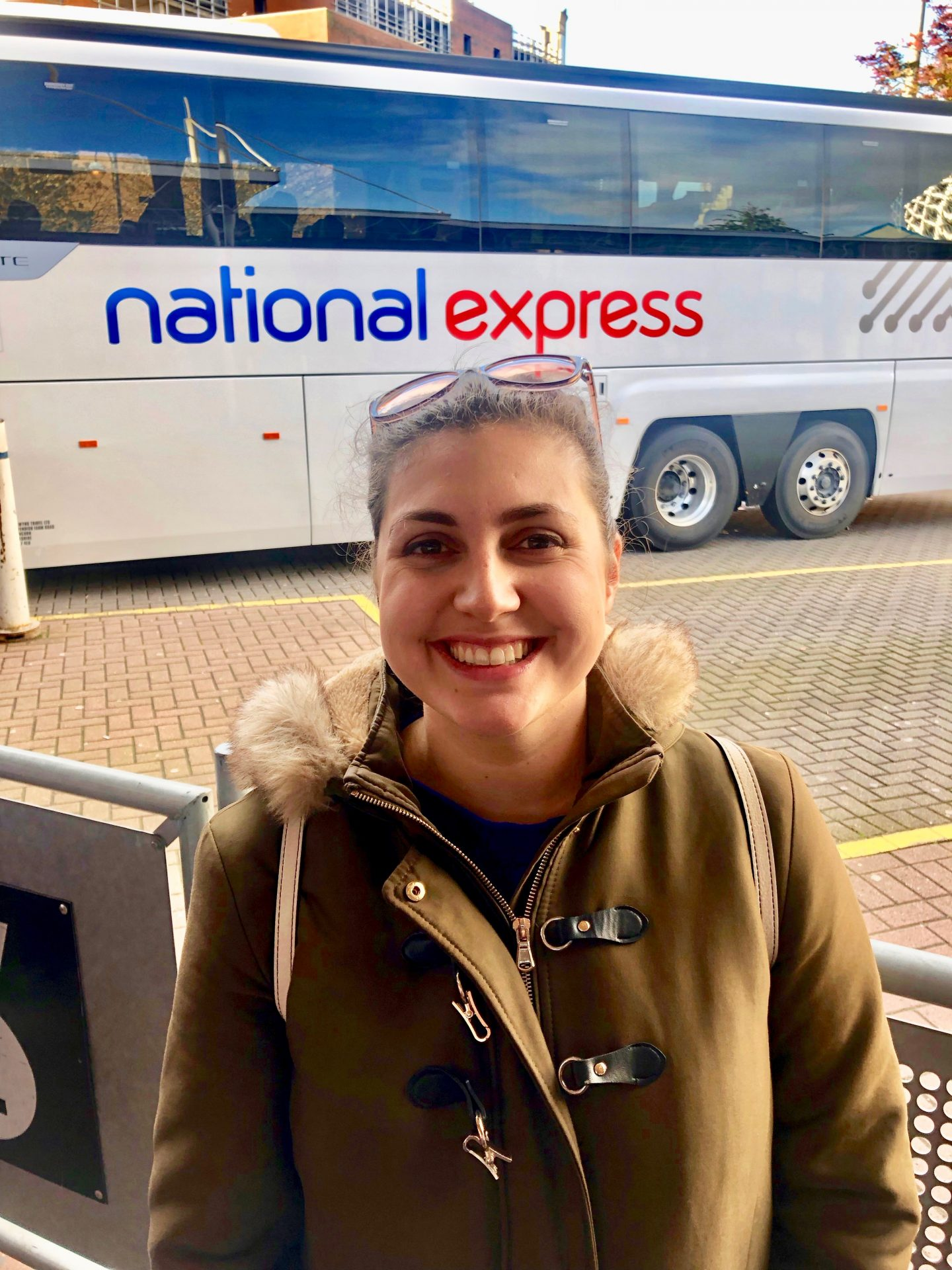 Best things to do in Liverpool: Nell stood next to a National Express Coach, smiling at the camera