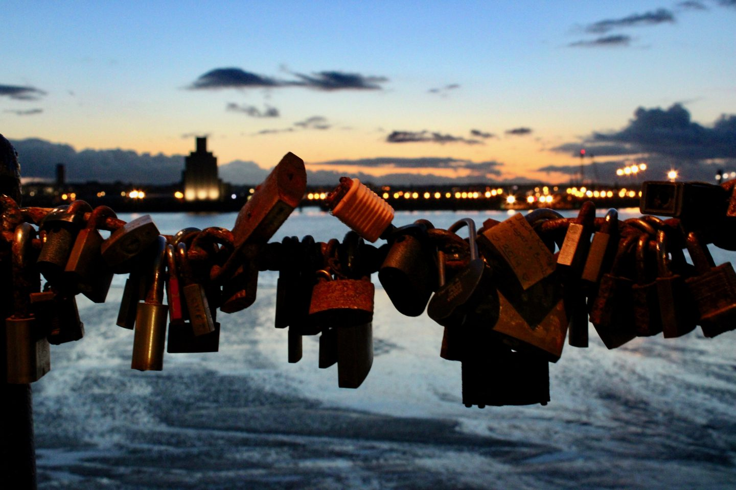 best things to do in Liverpool: padlocks on a bridge, with water and sunset behind