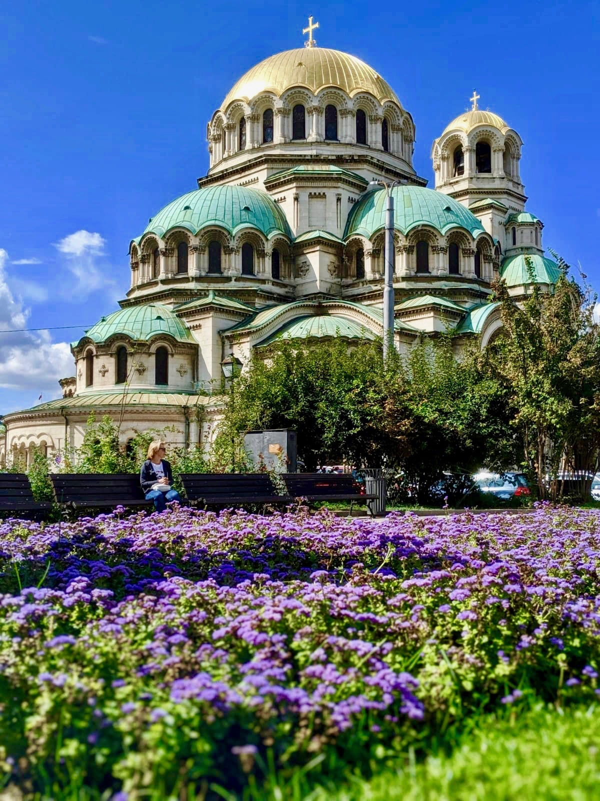 Istanbul Sofia Night Train: The Alexander Nevsky cathedral in Sofia. The sky is a bright blue in the background and there are bright purple flowers in the foreground.