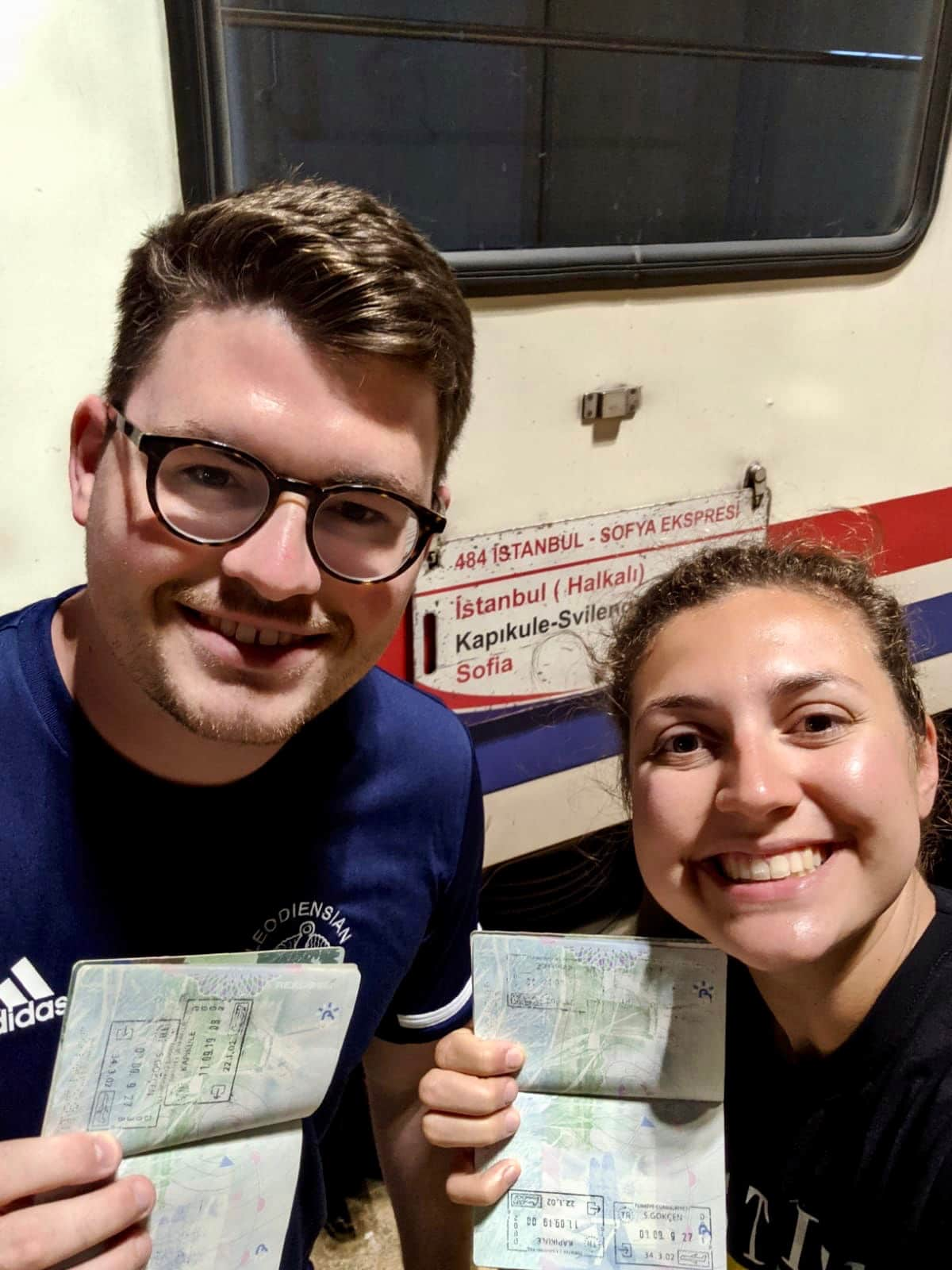 Selfie of man and woman at the Turkey Bulgaria border crossing, holding up their passports on the stamp page and smiling at the camera. The Istanbul to Sofia night train is in the background