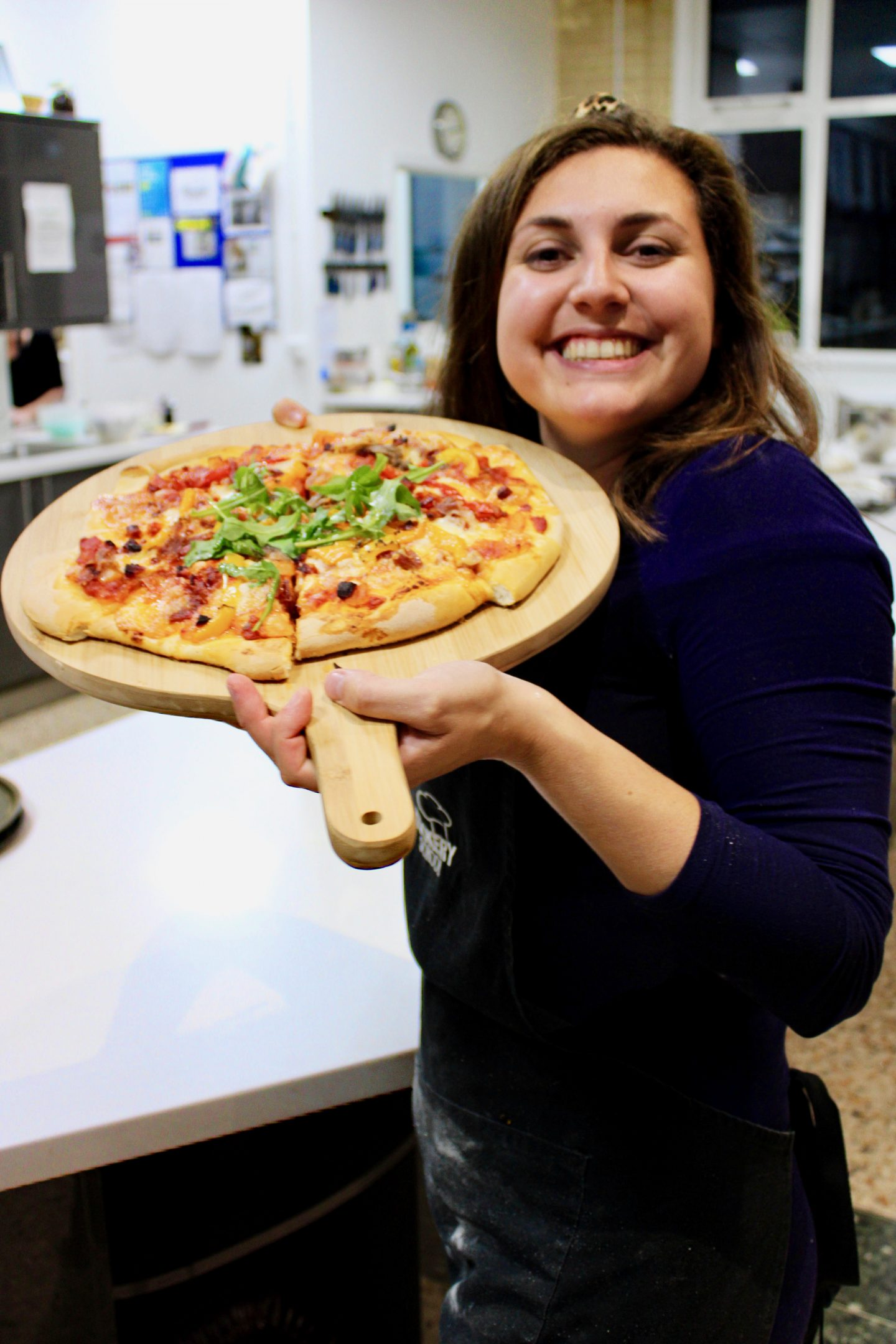 pizza making class leeds cookery school: Nell holding up her cooked pizza on a wooden board and smiling. She looks very happy with the results