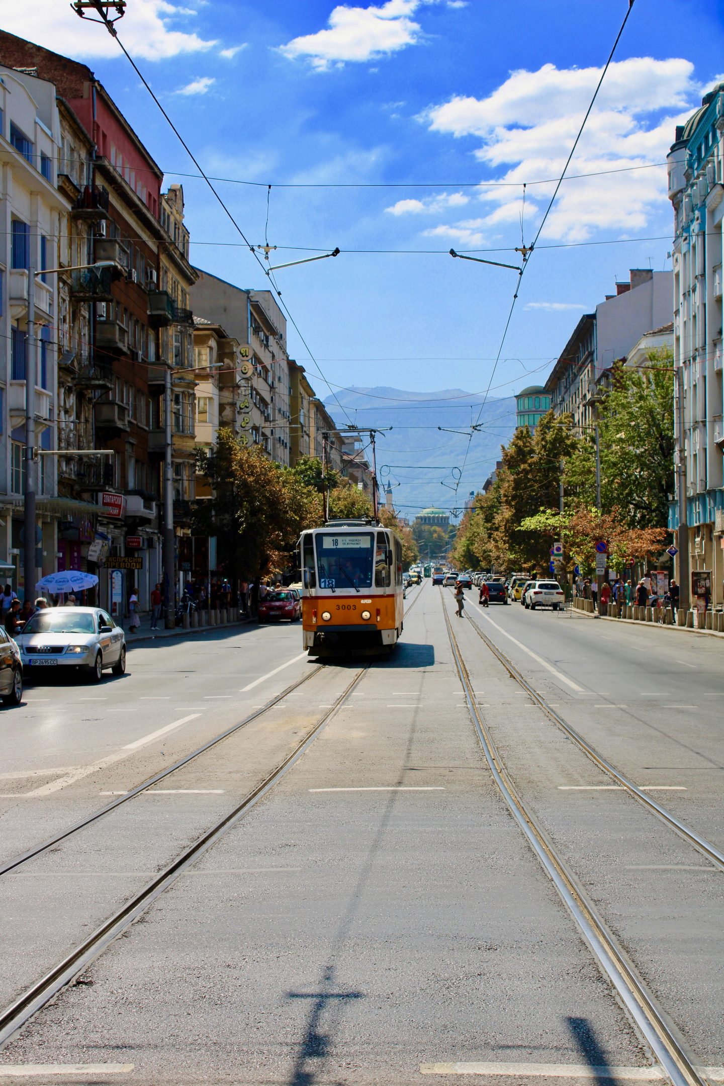 sofia city break: A yellow tram on a wide street in Sofia in the summer, with a blue sky and a green dome of a cathedral in the background