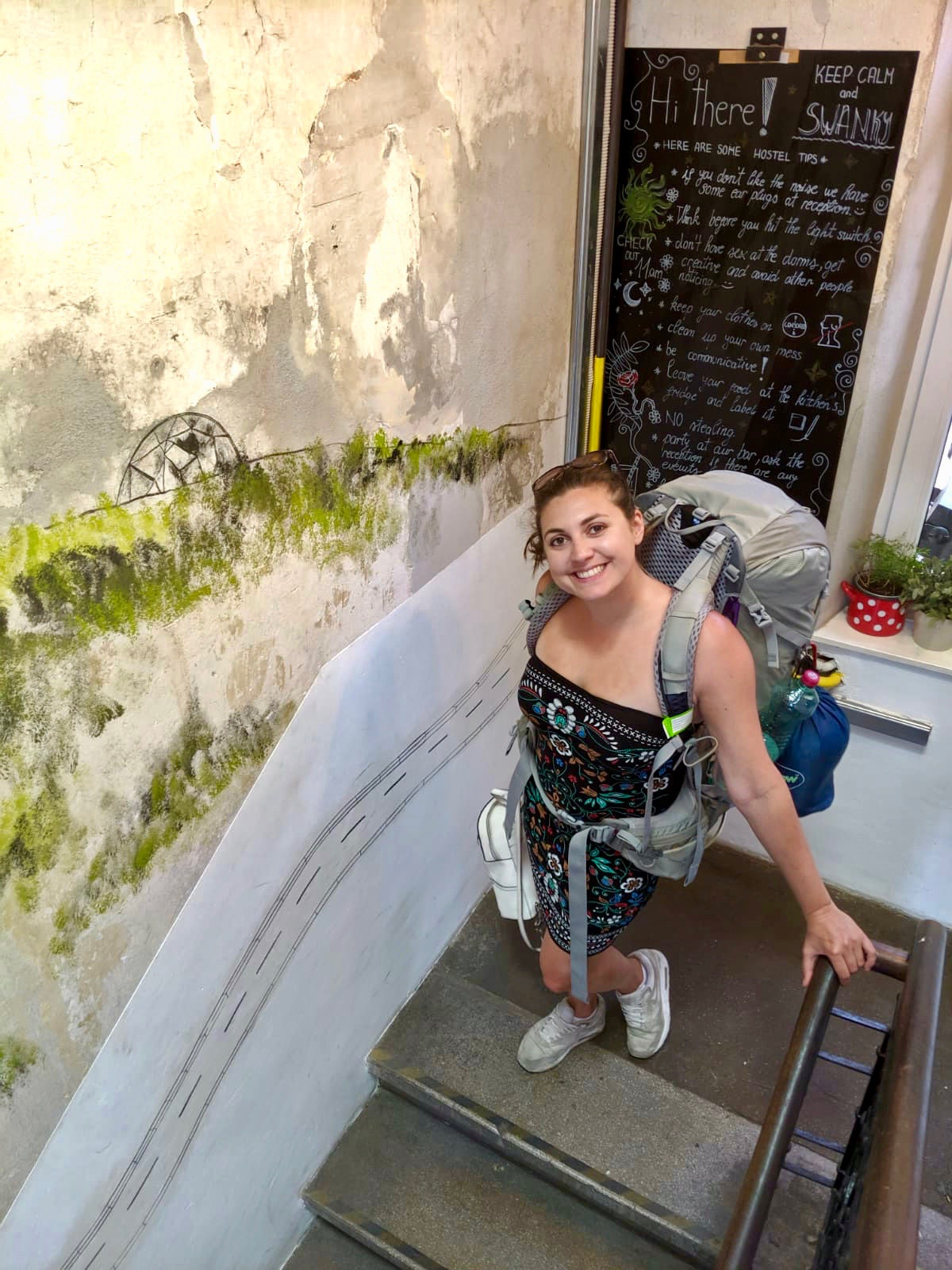 swanky mint hostel zagreb review: Nell wearing backpack on the stairs. She's looking up towards the camera and smiling