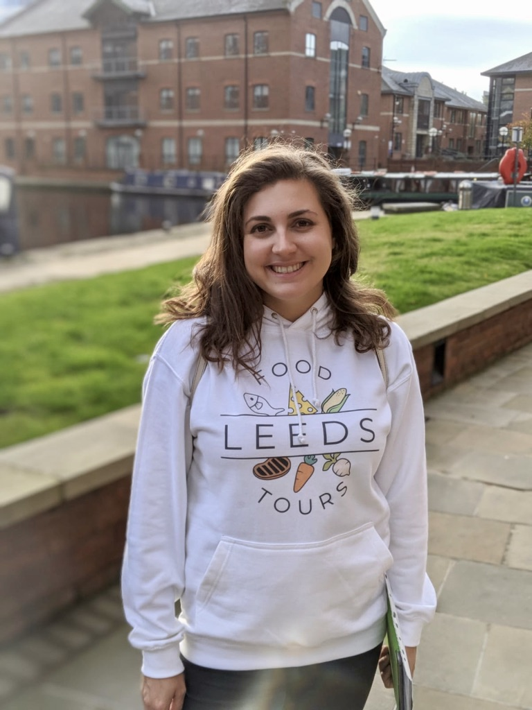 Nell wearing a Leeds Food Tours hoodie and smiling at the camera