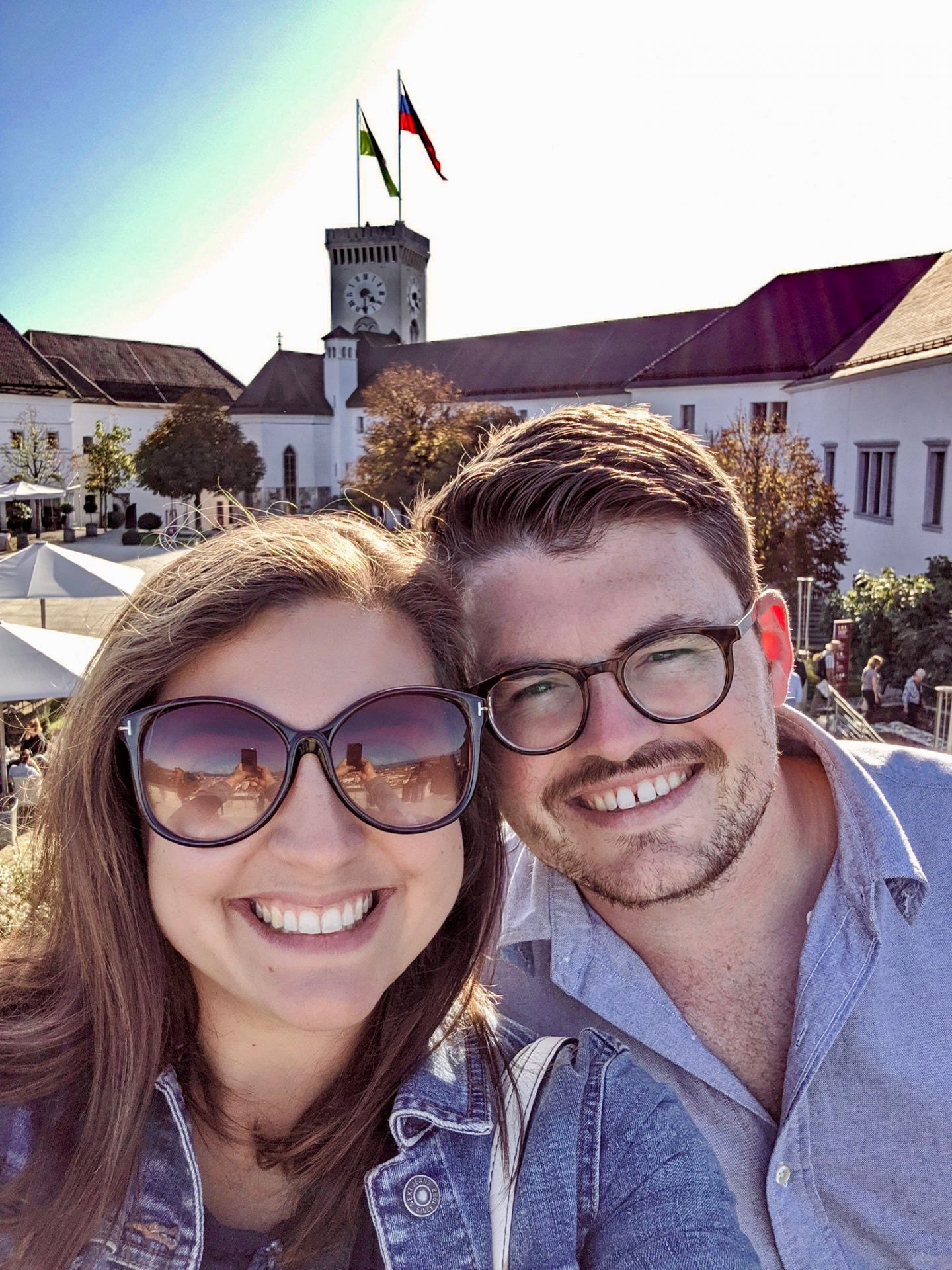 24 hours in Ljubljana food & wine: A selfie of man and women at Ljubljana castle with the castle tower in the background, a must do if you have 24 hours in Ljubljana