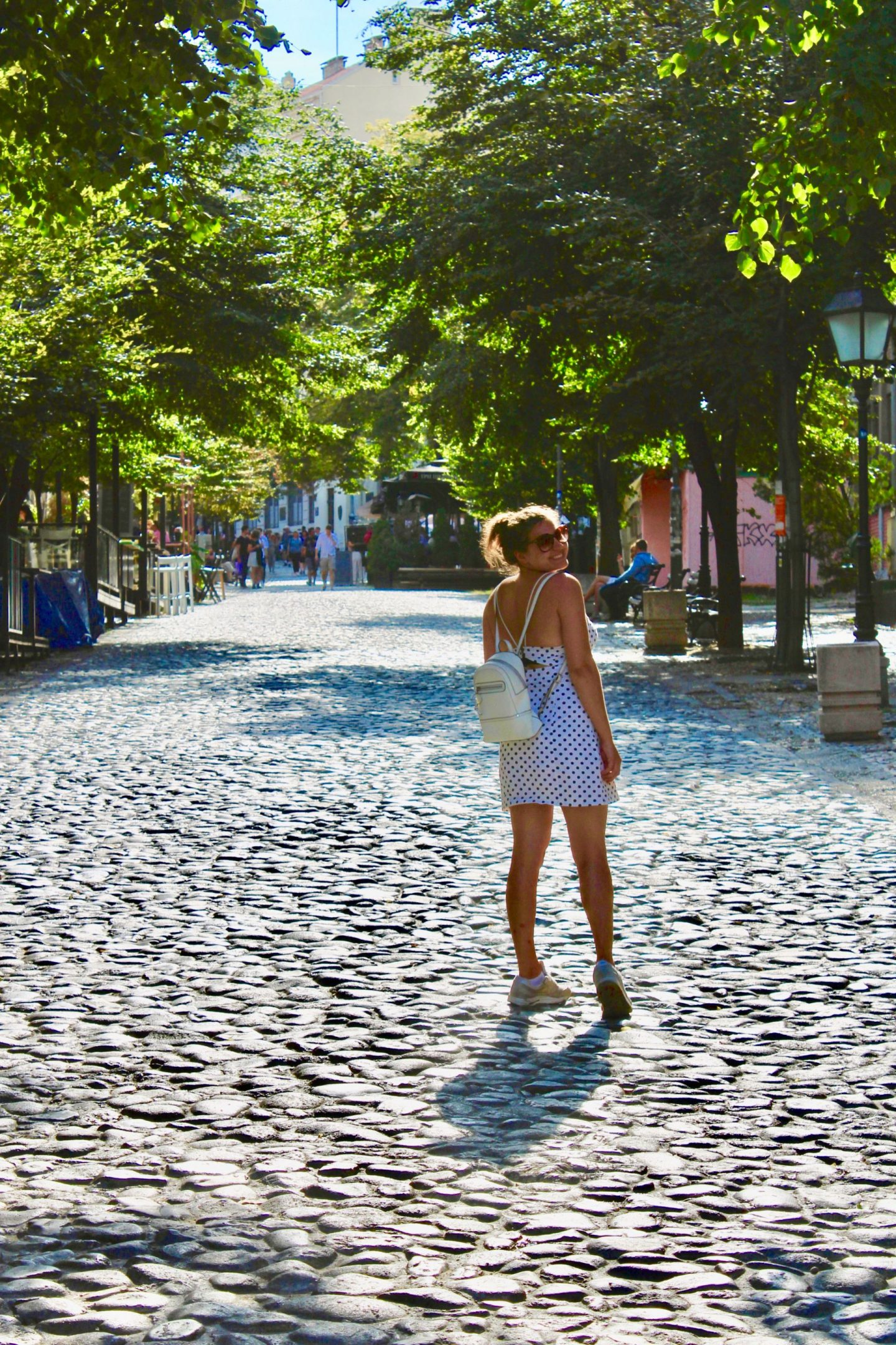 Girl in polkadot dress on a cobbled street, walking away from the camera but turning back to smile at it