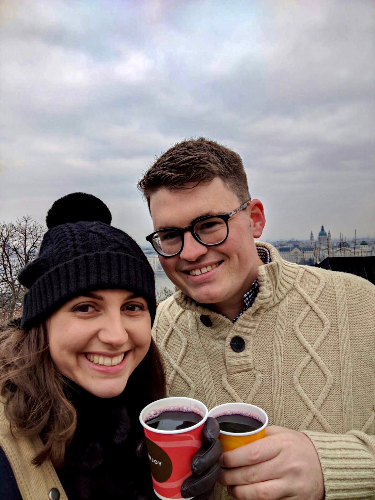 Couple smiling at the camera whilst they take a selfie, with a cup of mulled wine in hand