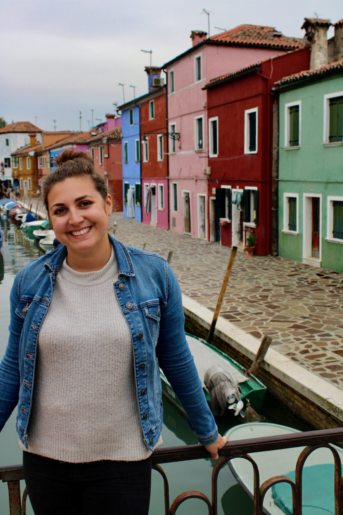 Nell on a bridge on the island of Burano, looking at the camera and smiling