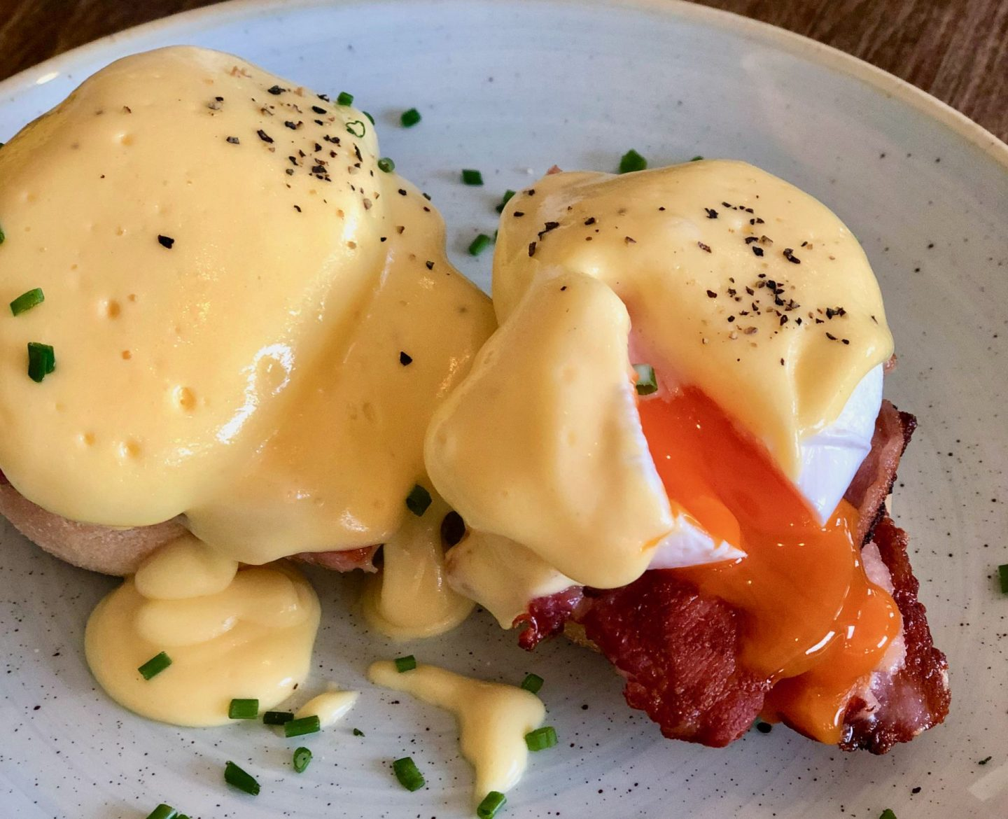 Close up of Eggs benedict, with the poached egg freshly burst and bright orange yolk spilling out