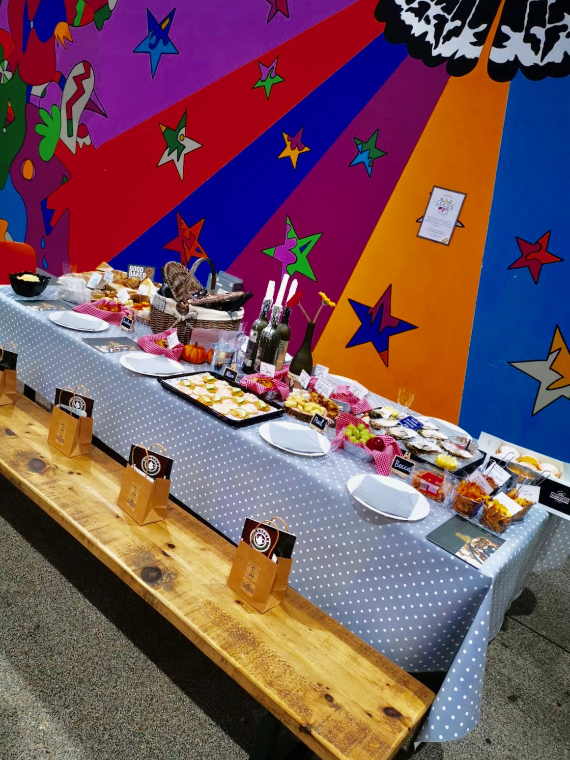Table in the market with food donated from various stall holders for the launch of Leeds Food Tours. On a polkadot table cloth are candles, a picnic basket, flowers and all sorts of foods including oysters, bread, cheeses and cakes