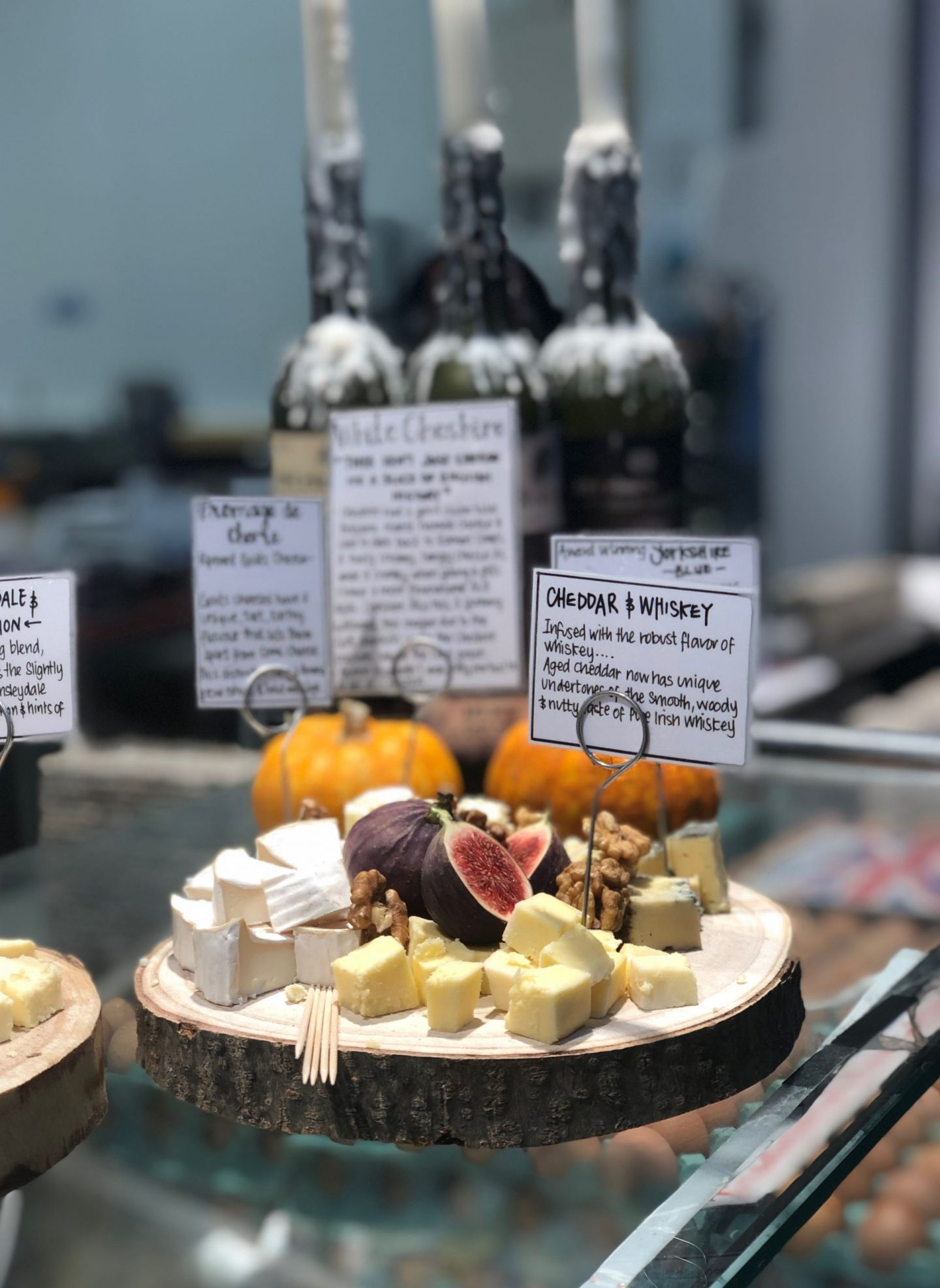 A selection of cheese samples on a wooden plate, with figs and walnuts in the centre. The cheeses have little signs in them showing what they are, with cheddar and whiskey in focus