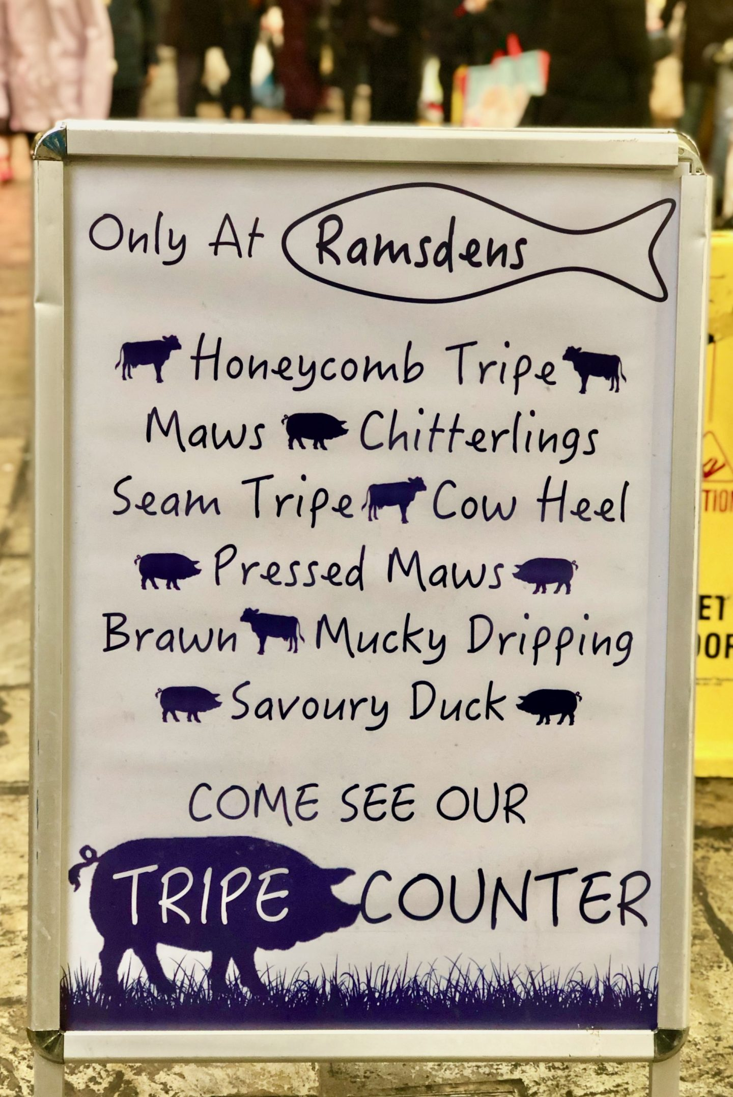 A sign for Ramsdens in Leeds Kirkgate Market displaying unusual products such as tripe, chitterlings and savoury duck