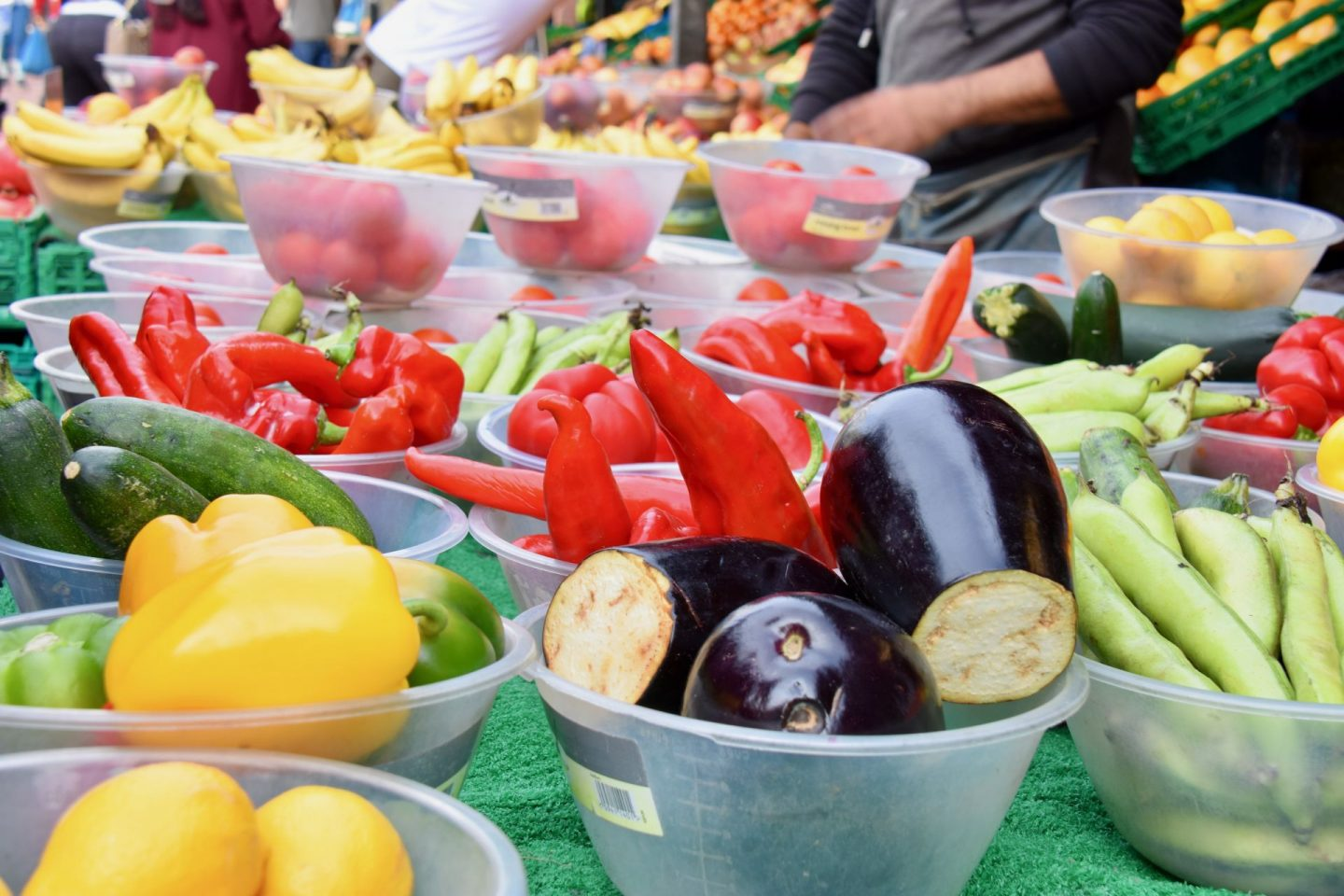 A selection of brightly coloured vegetables on an outside stall at Leeds Kirkgate market showing aubergines, different types of peppers, courgettes and tomoatoes, with some bananas in the background
