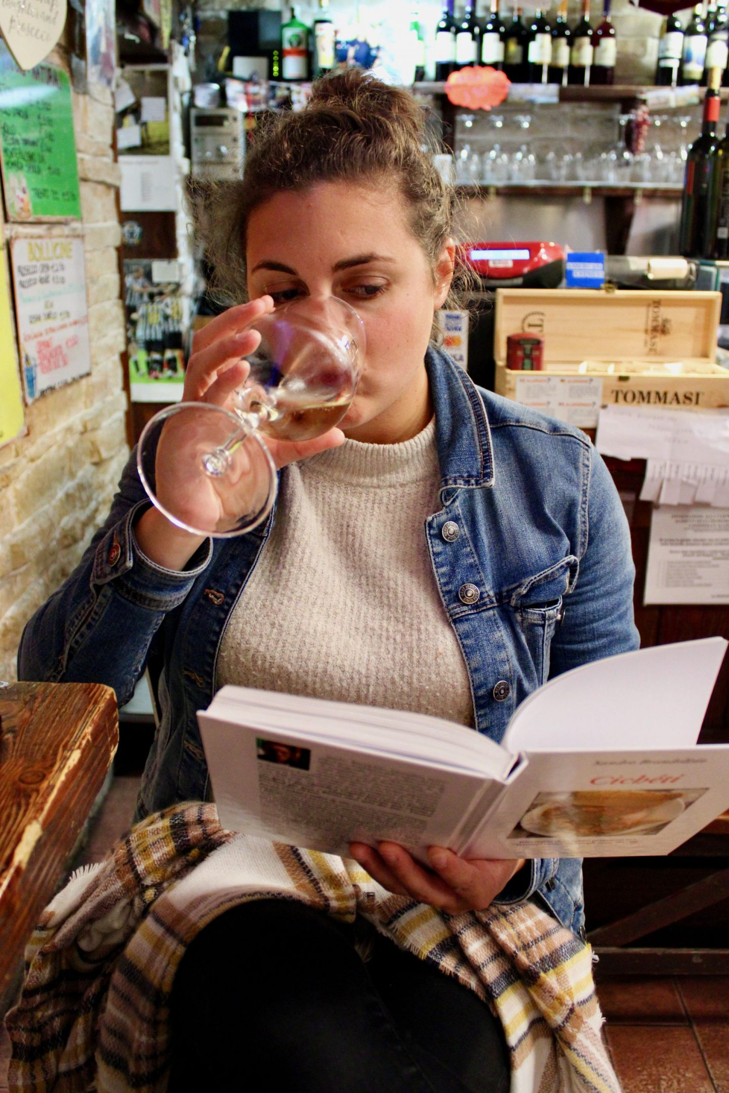 Nell drinking a glass of wine at a cicchetti bar in Venice whilst reading a book about cicchetti