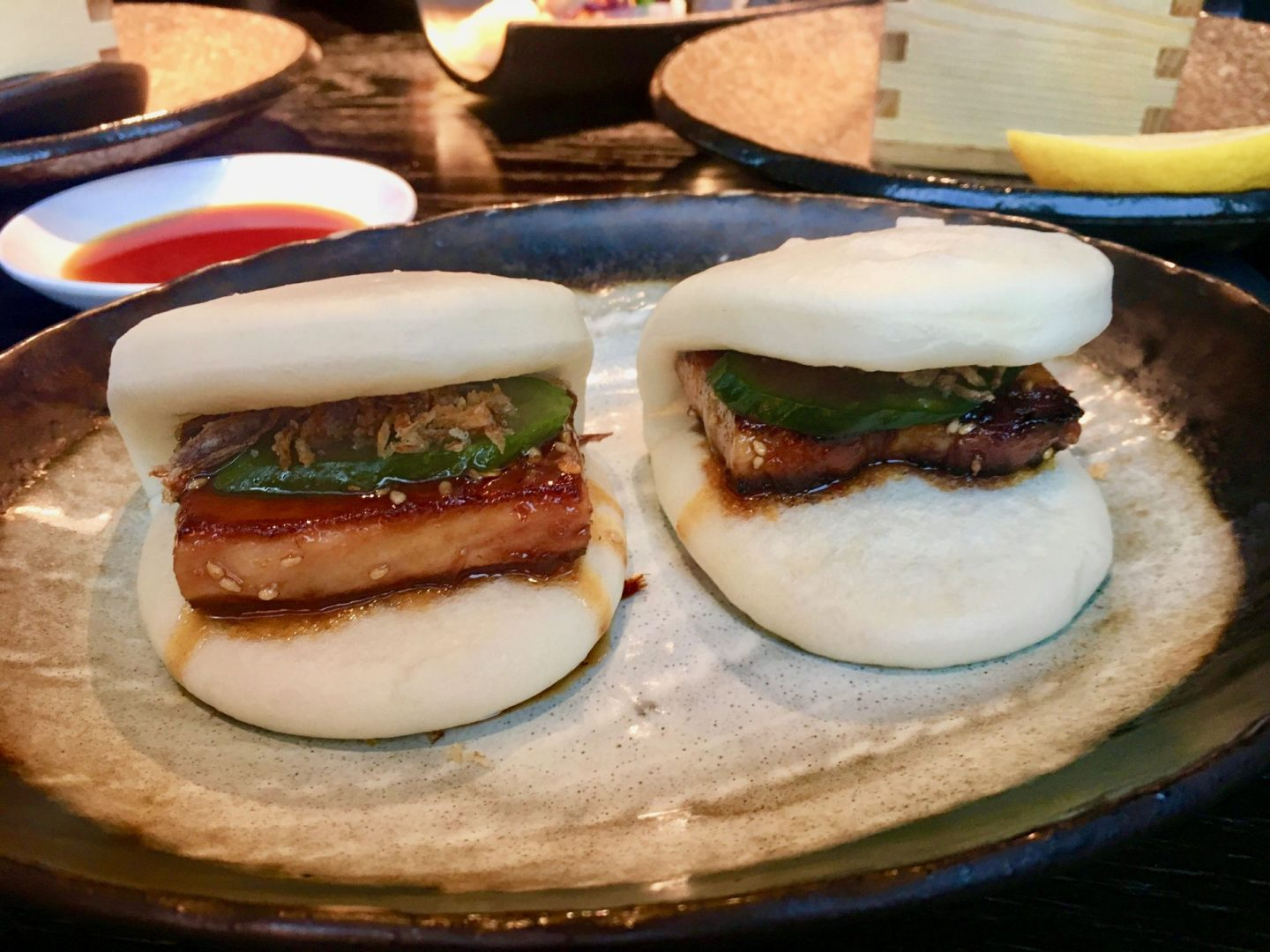 A pair of bao buns with pork belly inside, sat next to each other on a plain plate at issho sushi leeds