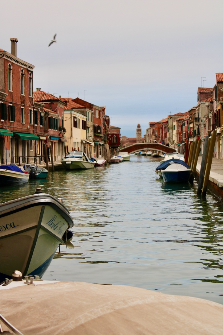 Image of Murano near Venice. Shows the canal with colourful buildings either side, a couple of boats moored up and early evening light