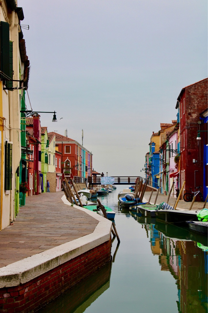 Burano near Venice, showing the canal meet the sea, with the sky and water the same colour and colourful buildings either side