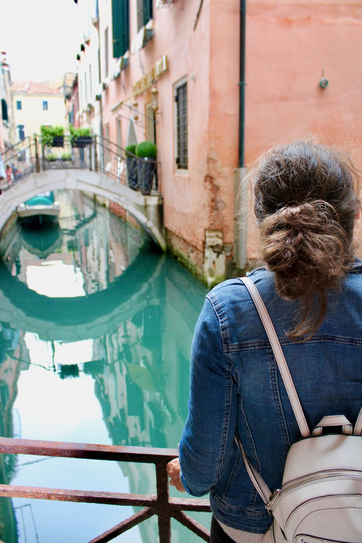 Nell looking out over a narrow canal in Venice with bright blue water