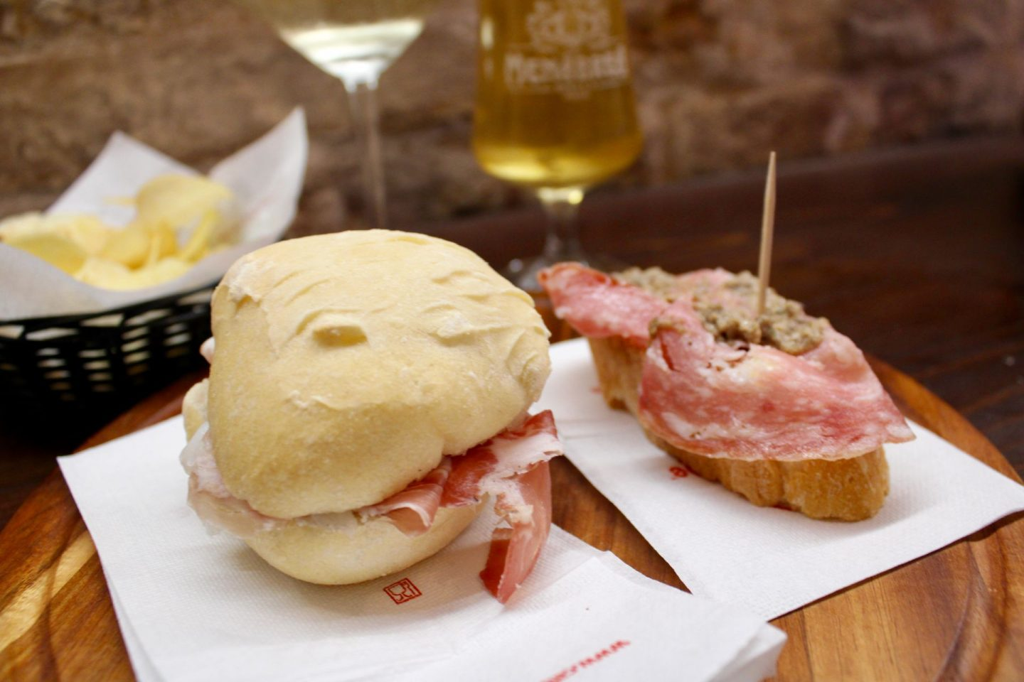 two bruschetta on a table, one is a small ham sandwich and the other is salami on bread topped with mushroom paste