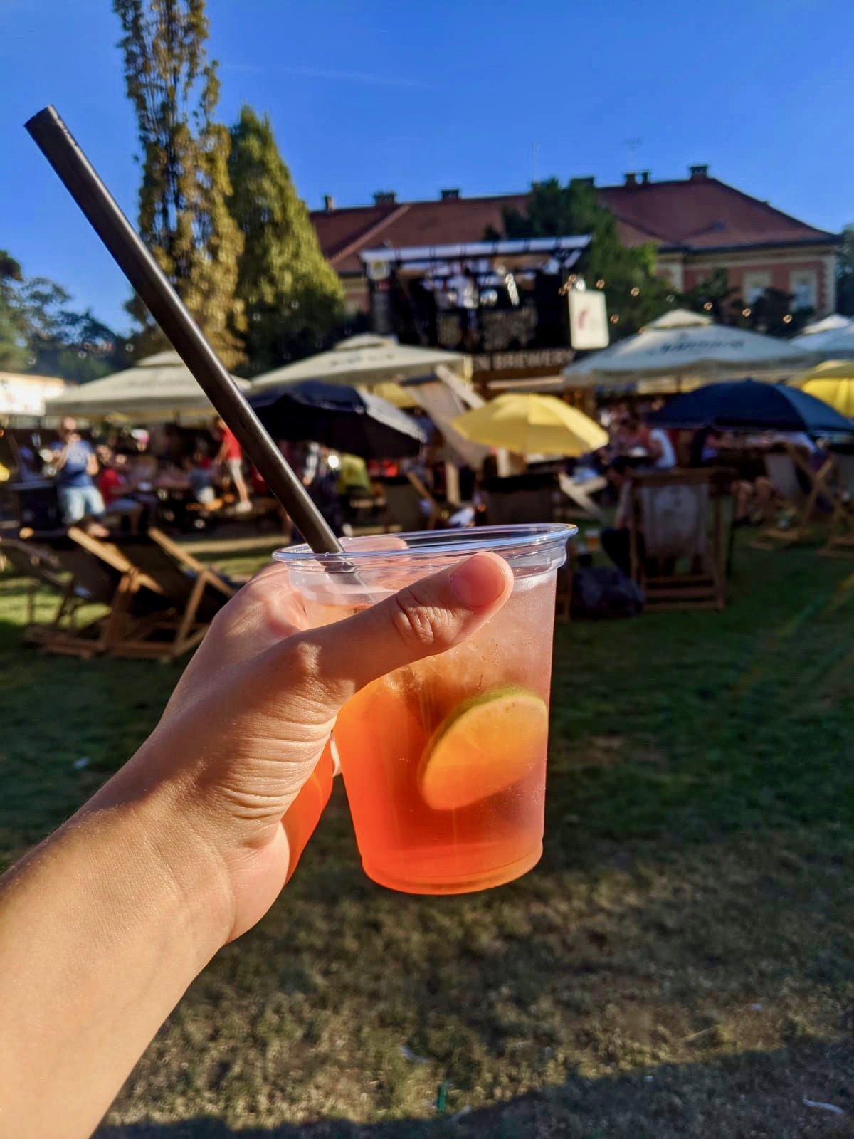 A hand holding an aperol spritz in a plastic cup at Zagreb burger festival