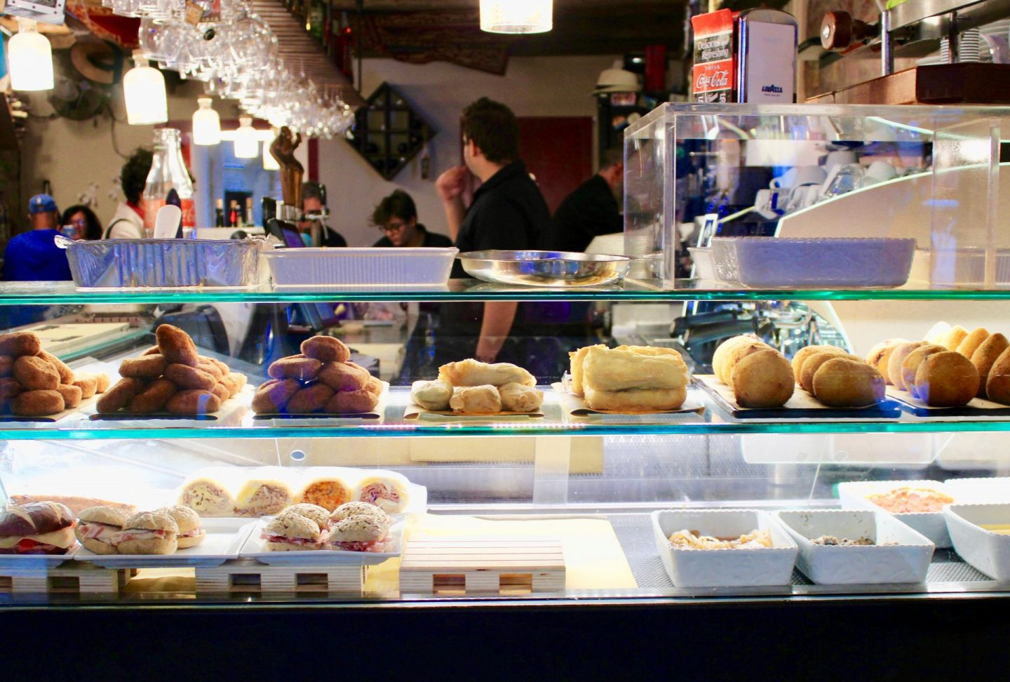 best cicchetti in Venice: a cicchetti bar with a wide range of food displayed behind a glass counter