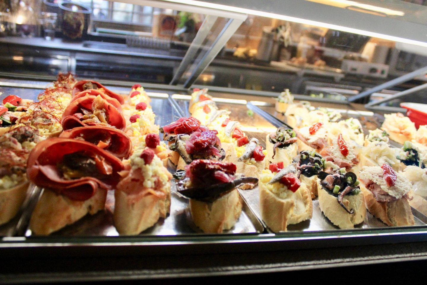 best cicchetti in Venice: a cicchetti bar with a wide range of food displayed behind a glass counter close up