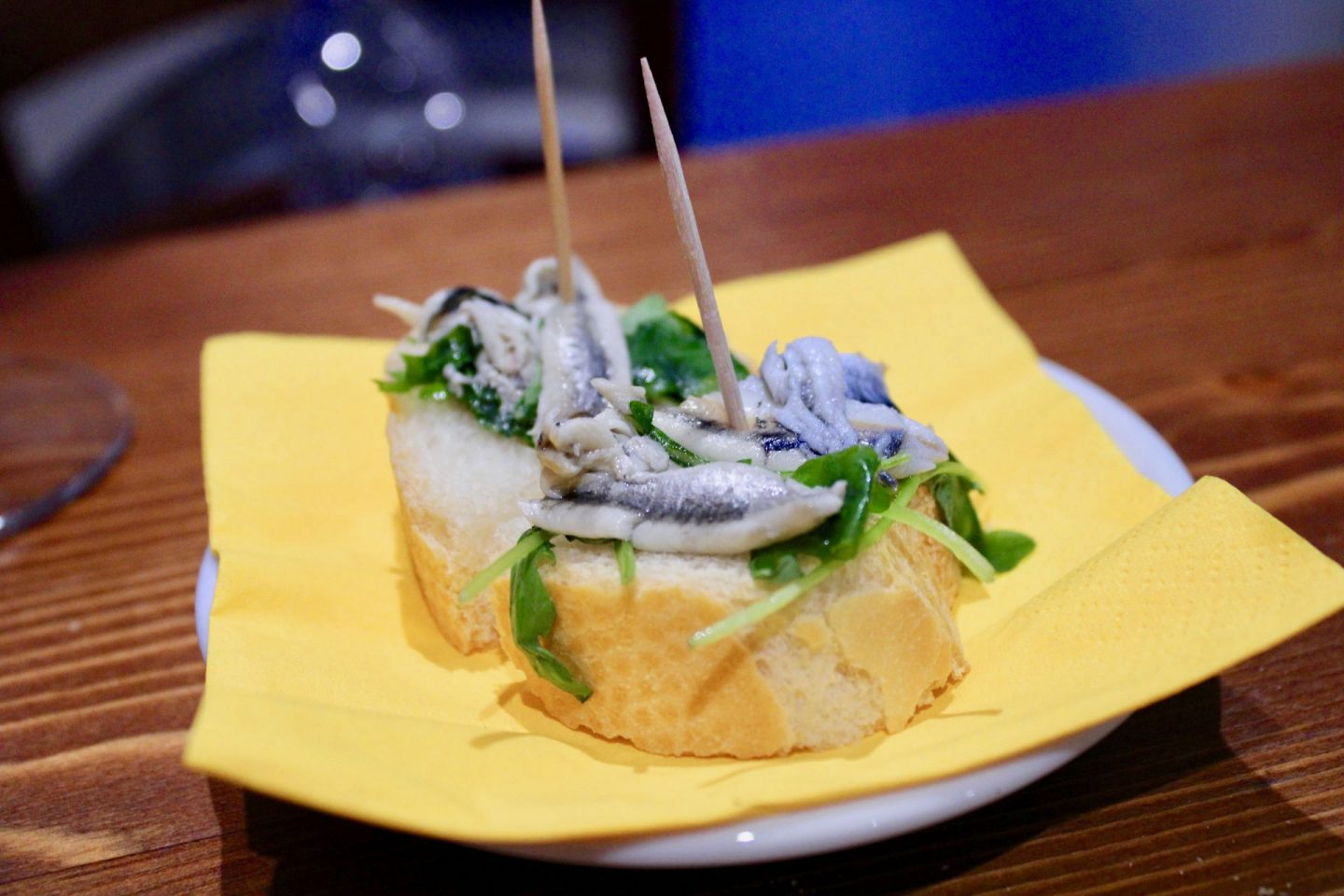 best cicchetti in Venice: bread topped with herring, served on a yellow napkin