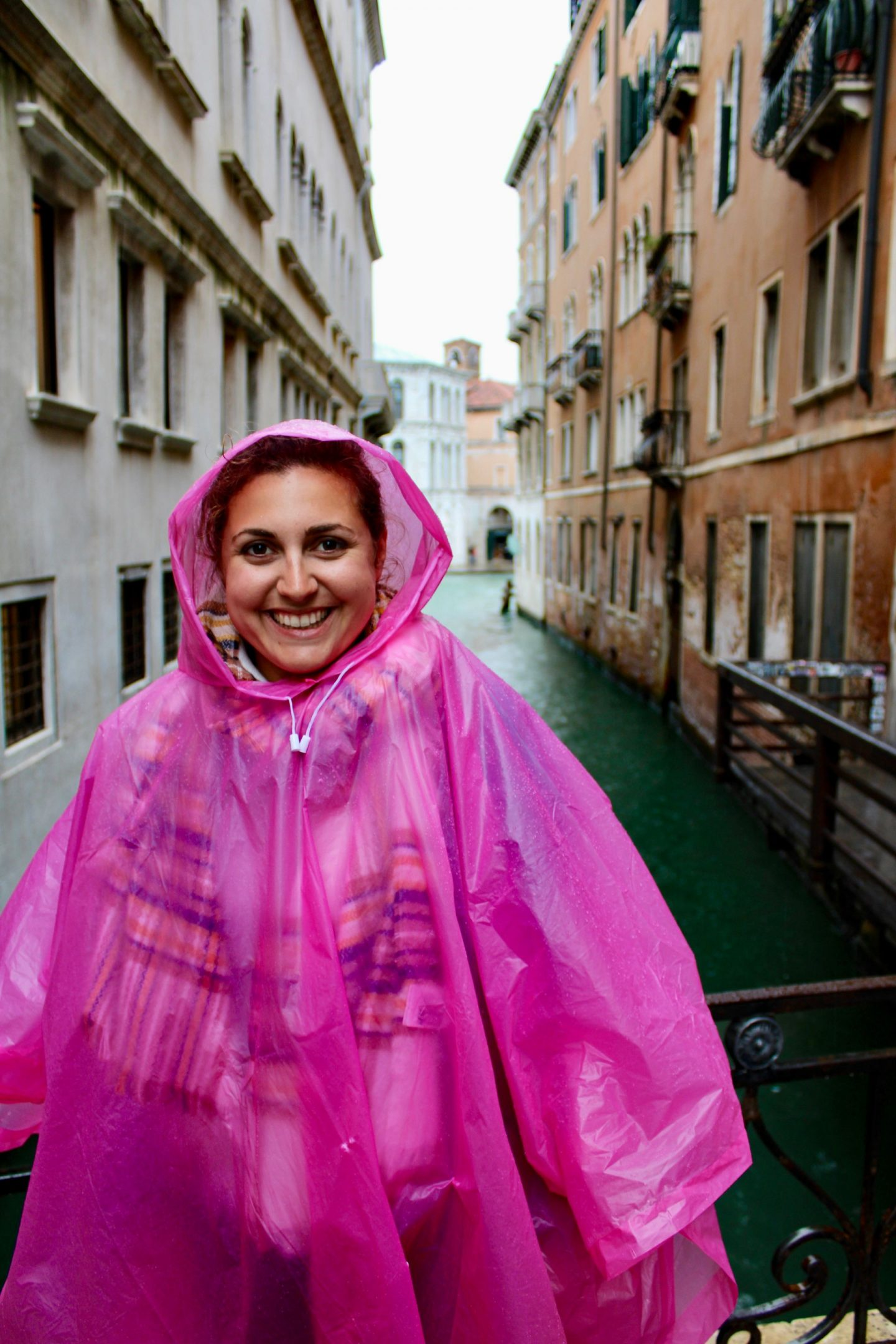 best cicchetti in Venice: Nell wearing a bright pink rain poncho and smiling at the camera with a canal behind her