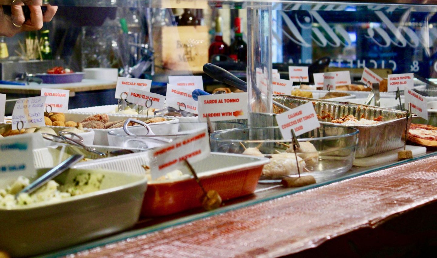 best cicchetti in Venice: a cicchetti bar with a wide range of food displayed behind a glass counter, with printed labels sticking out of each one
