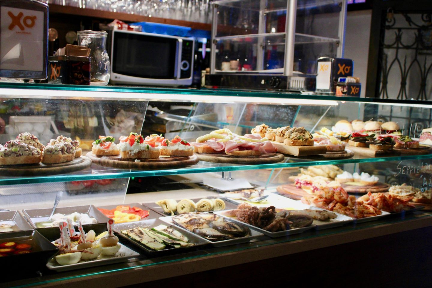 Travel tips for visiting Venice: a cicchetti bar in venice, showing a selection of small snacks