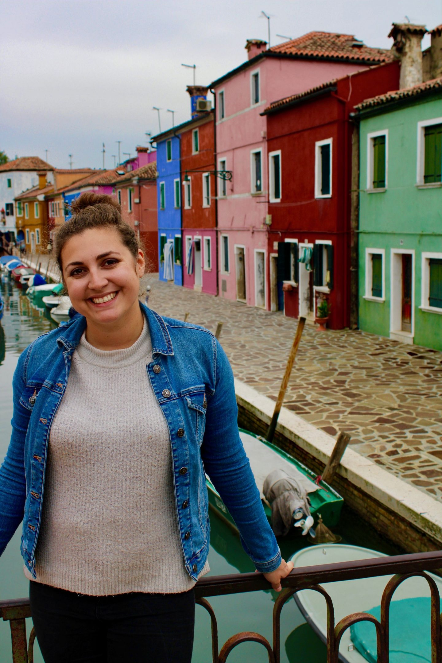 Nell on a bridge on the island of Burano in Venice, looking at the camera and smiling