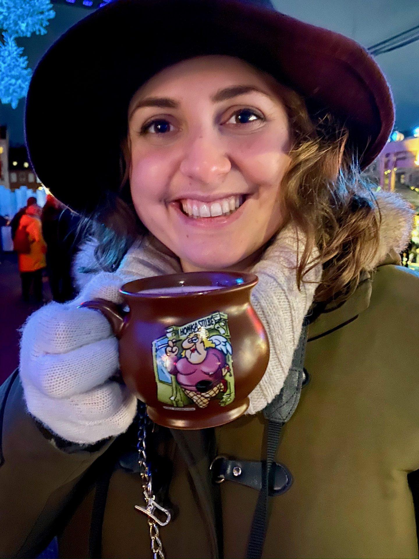 Nell holding a mug of mulled wine and smiling at the camera at the Santa Pauli Christmas market in Hamburg